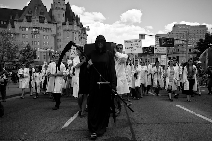 Scientists in lab coats hold a funeral for evidence based decision-making.